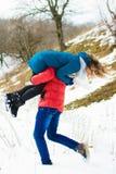 Ο τύπος φέρνει τη φίλη του στον ώμο του στο χειμερινό λιβάδι στοκ φωτογραφία με δικαίωμα ελεύθερης χρήσης