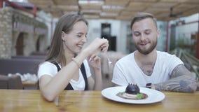 Ο τύπος φλερτάρει με το κορίτσι Ένα ζεύγος γελά σε έναν καφέ Εξοικείωση και χρονολόγηση φιλμ μικρού μήκους