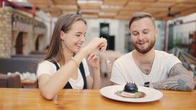 Ο τύπος φλερτάρει με το κορίτσι Ένα ζεύγος γελά σε έναν καφέ Εξοικείωση και χρονολόγηση απόθεμα βίντεο