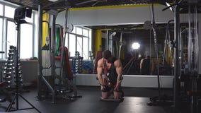 Ο τύπος bodybuilder, εκτελεί την άσκηση με τη μηχανή άσκησης στους θωρακικούς μυς, στη γυμναστική απόθεμα βίντεο