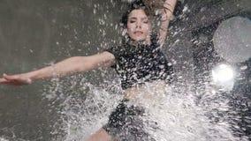 Ο υγρός θηλυκός χορευτής στο μαύρο σώμα εκτελεί ένα πήδημα στη βροχή και τους παφλασμούς του νερού Το κορίτσι χορευτών που χόρεψε φιλμ μικρού μήκους