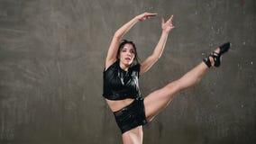 Ο υγρός νέος χορευτής γυναικών στο μαύρο κομπινεζόν είναι συναισθηματικός σύγχρονος χορός χορού κάτω από τις πτώσεις του νερού στ απόθεμα βίντεο