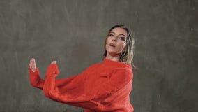 Ο υγρός χορευτής κοριτσιών στο κόκκινο πουλόβερ και τα μαύρα σορτς εκτελεί το σύγχρονο χορό στη βροχή και τους παφλασμούς του νερ φιλμ μικρού μήκους