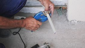 Ο υδραυλικός κόβει τον πλαστικό σωλήνα μετάλλων με έναν κόπτη σωλήνων Ψαλίδι για μια πλαστική κοπή σωλήνων Έννοια κατασκευής απόθεμα βίντεο