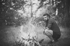 Ο υλοτόμος ατόμων με το τσεκούρι εξετάζει τη φλόγα φωτιών Στοκ Φωτογραφία