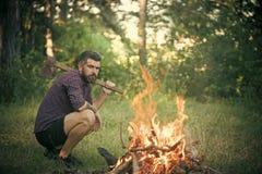 Ο υλοτόμος ατόμων με το τσεκούρι εξετάζει τη φλόγα φωτιών Στοκ φωτογραφία με δικαίωμα ελεύθερης χρήσης
