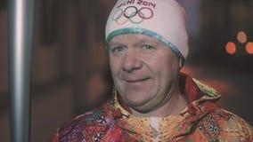 Ολυμπιακή φλόγα φυλών ηλεκτρονόμων σε Άγιο Πετρούπολη Ενήλικες συγκινήσεις μεριδίου torchbearer μετά από να τρέξει απόθεμα βίντεο