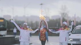 Ολυμπιακός φανός του Sochi φυλών ηλεκτρονόμων σε Άγιο Πετρούπολη Δύο χέρια κυμάτων torchbearers Φλόγα περασμάτων στιγμής φιλμ μικρού μήκους