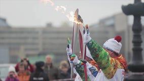 Ολυμπιακός φανός του Sochi φυλών ηλεκτρονόμων σε Άγιο Πετρούπολη Δύο torchbearers στο ομοιόμορφο κύμα φλογών λαβής δίνουν φιλμ μικρού μήκους
