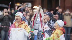 Ολυμπιακός φανός του Sochi φυλών ηλεκτρονόμων σε Άγιο Πετρούπολη Ηλικίας φλόγα περασμάτων γυναικών στον άνδρα torchbearers φιλμ μικρού μήκους