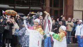Ολυμπιακός φανός του Sochi φυλών ηλεκτρονόμων σε Άγιο Πετρούπολη Ηλικίας θηλυκή φλόγα περασμάτων torchbearer στο άτομο Χαμόγελο απόθεμα βίντεο