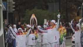 Ολυμπιακός φανός του Sochi φυλών ηλεκτρονόμων σε Άγιο Πετρούπολη Ομάδα των χεριών κυμάτων torchbearers Διάβαση της φλόγας φιλμ μικρού μήκους