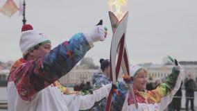 Ολυμπιακός φανός του Sochi φυλών ηλεκτρονόμων σε Άγιο Πετρούπολη Στιγμή της φλόγας περασμάτων torchbearers Χέρια κυμάτων απόθεμα βίντεο