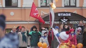 Ολυμπιακός φανός του Sochi φυλών ηλεκτρονόμων σε Άγιο Πετρούπολη Το πλήθος των ανθρώπων εξετάζει το τρέξιμο του torchbearer απόθεμα βίντεο