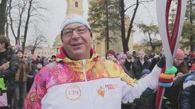 Ολυμπιακός φανός του Sochi φυλών ηλεκτρονόμων σε Άγιο Πετρούπολη Το Torchbearer δίνει τη συνέντευξη κεκλεισμένων των θυρών φρούρι απόθεμα βίντεο