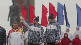 Ολυμπιακός φανός του Sochi φυλών ηλεκτρονόμων σε Άγιο Πετρούπολη Το καίγοντας κερί λαβής ατόμων αναφλέγει τη φλόγα στη σκηνή απόθεμα βίντεο