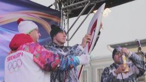 Ολυμπιακός φανός του Sochi φυλών ηλεκτρονόμων σε Άγιο Πετρούπολη Φλόγα εγκαυμάτων Torchbearer στη σκηνή έναρξη τρεξίματος απόθεμα βίντεο