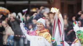 Ολυμπιακός φανός του Sochi φυλών ηλεκτρονόμων σε Άγιο Πετρούπολη Φλόγα περασμάτων Torchbearer Τοποθέτηση στη κάμερα Χαμόγελο φιλμ μικρού μήκους