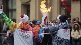 Ολυμπιακός φανός του Sochi φυλών ηλεκτρονόμων σε Άγιο Πετρούπολη Φλόγα περασμάτων torchbearer πίσω πλευράς Θέστε στη κάμερα απόθεμα βίντεο