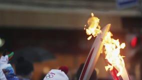 Ολυμπιακός φανός του Sochi φυλών ηλεκτρονόμων σε Άγιο Πετρούπολη Καίγοντας φανός δύο Διάβαση της φλόγας από τα torchbearers απόθεμα βίντεο