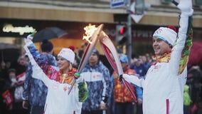 Ολυμπιακός φανός του Sochi φυλών ηλεκτρονόμων σε Άγιο Πετρούπολη Αρσενικά, θηλυκά χέρια κυμάτων torchbearers Φλόγα περασμάτων απόθεμα βίντεο