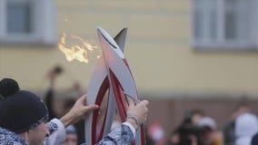 Ολυμπιακός φανός του Sochi φυλών ηλεκτρονόμων σε Άγιο Πετρούπολη Καίγοντας φανός δύο από κοινού Στιγμή της φλόγας περασμάτων απόθεμα βίντεο