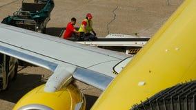 Ο υπάλληλος αερολιμένων παίρνει τις αποσκευές από το αεροπλάνο απόθεμα βίντεο