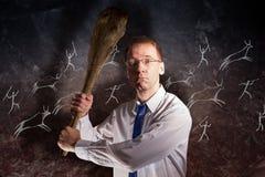 Ο υπάλληλος γραφείων με ένα ρόπαλο στα χέρια του απειλεί στα πλαίσια των πρωτόγονων γλυπτικών βράχου Στοκ Φωτογραφίες