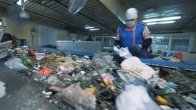 Ο υπάλληλος εργοστασίων θηλυκών ταξινομεί τα απόβλητα για την περαιτέρω ανακύκλωση απόβλητα ανακύκλωσης φυ&ta φιλμ μικρού μήκους