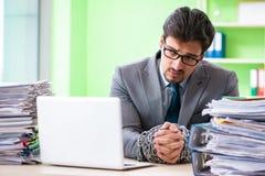 Ο υπάλληλος που αλυσοδένεται στο γραφείο του λόγω του φόρτου εργασίας Στοκ Εικόνα