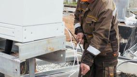 Ο υπάλληλος στο ομοιόμορφο κράνος προετοιμάζει το καλώδιο για το μοντάρισμα από τον πόλο μετάλλων απόθεμα βίντεο