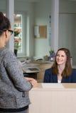 Ο υπάλληλος χαμογελά σε έναν πελάτη Στοκ φωτογραφία με δικαίωμα ελεύθερης χρήσης