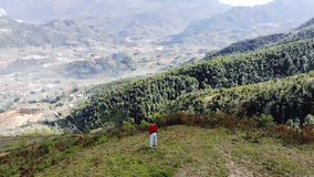 Ο υπαίθριος περίπατος κοριτσιών στην αιχμή, έχει μια καλή άποψη πάνω από τη σειρά βουνών, για να κοιτάξει μακριά στην απόσταση, σ φιλμ μικρού μήκους