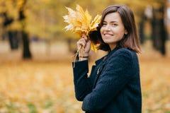 Ο υπαίθριος πυροβολισμός της όμορφης χαλαρωμένης γυναίκας αναπνέει το καθαρό αέρα, που είναι στην καλή διάθεση, φέρνει τα κίτρινα στοκ εικόνες