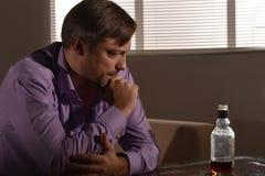 Ο λυπημένος νεαρός άνδρας πίνει το ουίσκυ Στοκ Φωτογραφία