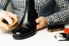 Ο υποδηματοποιός s δίνει τα καθαρίζοντας παπούτσια με μια βούρτσα πέρα από το pla εργασίας του στοκ φωτογραφίες με δικαίωμα ελεύθερης χρήσης