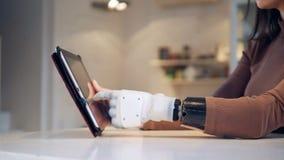 Ο υπολογιστής ταμπλετών παίρνει χρησιμοποιημένος από ένα θηλυκό με έναν βιονικό βραχίονα φιλμ μικρού μήκους