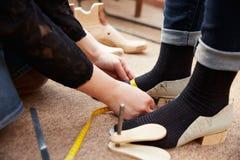 Ο υποδηματοποιός που μετρά τα πόδια πελατών, κλείνει επάνω Στοκ Εικόνες