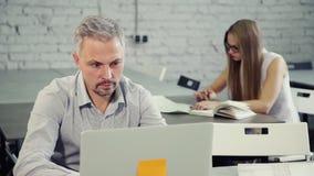 Ο υψηλός επαγγελματικός αρσενικός σχεδιαστής κάθεται στο γραφείο και εργάζεται στο νέο πρόγραμμα μάρκετινγκ απόθεμα βίντεο
