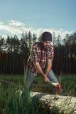Ο υλοτόμος με τη γενειάδα, το καπέλο και το πουκάμισο κόβουν ένα δέντρο Στοκ φωτογραφία με δικαίωμα ελεύθερης χρήσης