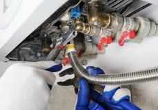 Ο υδραυλικός συνδέεται με το λέβητα αερίου σωλήνων στοκ εικόνες