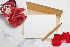 Ο φάκελος του Κραφτ προτύπων και μια επιστολή με ένα καρδιά-διαμορφωμένο δώρο με ένα κόκκινο υποκύπτουν και αυξήθηκαν πέταλα, ευχ Στοκ Φωτογραφίες