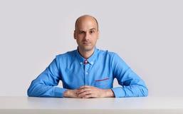Ο φαλακρός επιχειρηματίας κάθεται στο γραφείο Στοκ Εικόνες