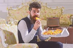 Ο φαλλοκράτης στα κλασικά ενδύματα πεινασμένα, στο έκπληκτο πρόσωπο, φέτα δαγκωμάτων της πίτσας, τρώει, εσωτερικό υπόβαθρο Παράδο στοκ φωτογραφίες