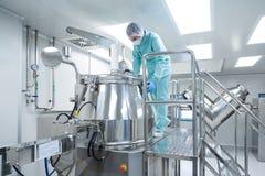 Ο φαρμακευτικός εργαζόμενος ατόμων εργοστασίων στη προστατευτική ενδυμασία ενεργοποιεί τη γραμμή παραγωγής στις αποστειρωμένες συ στοκ φωτογραφίες