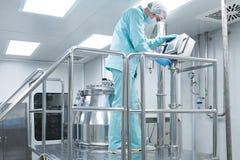 Ο φαρμακευτικός εργαζόμενος ατόμων εργοστασίων στη προστατευτική ενδυμασία ενεργοποιεί τη γραμμή παραγωγής στις αποστειρωμένες συ στοκ εικόνες