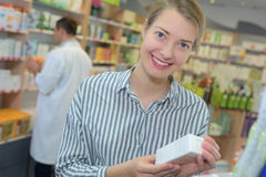 Ο φαρμακοποιός έχει δώσει το κιβώτιο ιατρικής στον πελάτη στο φαρμακείο στοκ εικόνα με δικαίωμα ελεύθερης χρήσης