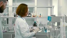 Ο φαρμακοποιός γυναικών παρουσιάζει εργαστηριακό βοηθό πώς να ρυθμίσει τον εξοπλισμό φιλμ μικρού μήκους