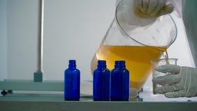 Ο φαρμακοποιός χύνει το υγρό στο φλυτζάνι μέτρου φιλμ μικρού μήκους