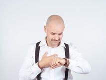 Ο φαλακρός επιχειρηματίας εξετάζει το ρολόι του Στοκ εικόνα με δικαίωμα ελεύθερης χρήσης
